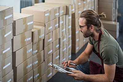Man using digital tablet to check boxed products in factory storeroom - p924m1422840 by Zero Creatives
