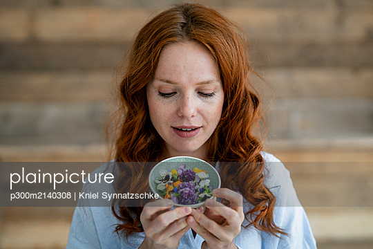 Portrait of redheaded woman looking at blossoms in a bowl - p300m2140308 by Kniel Synnatzschke