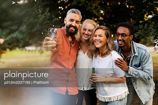 Smiling friends taking selfie - p312m2237159 by Plattform