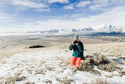Female hiker photographing with camera while kneeling on snowy field against mountains - p1166m1543146 by Cavan Images