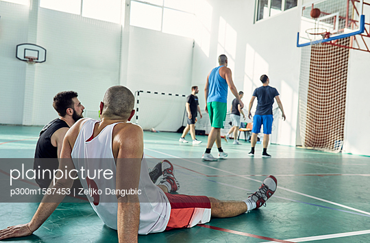 Basketball players during break, sitting on court - p300m1587453 von Zeljko Dangubic