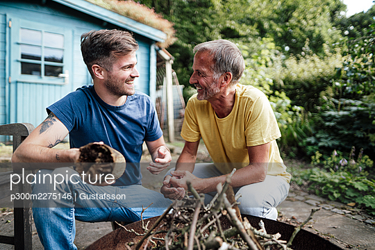 Son holding firewood discussing with father while crouching in backyard - p300m2275146 by Gustafsson