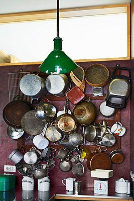 Pots and pans hanging on wall rack below transom window and vintage pendant lamp with green metal lampshade - p1183m995776 by Bressan e Trentani