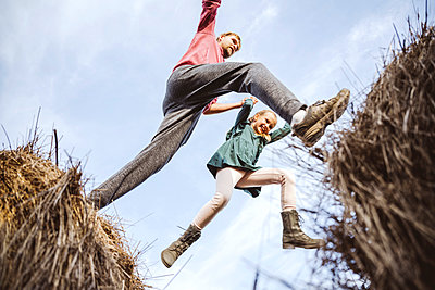 Father and daughter jumping over hay bales with excitement - p300m2225505 by Ekaterina Yakunina