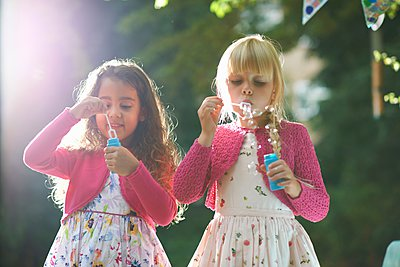 Two cute girls blowing bubbles in garden - p429m1062240f by Peter Muller