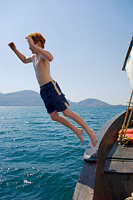 Young boy jumps off thel dhow while on a trip from Pumulani Lodge - p6521865 by John Warburton-Lee
