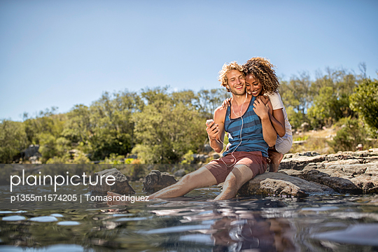 Young couple takes a break on the riverbank - p1355m1574205 by Tomasrodriguez