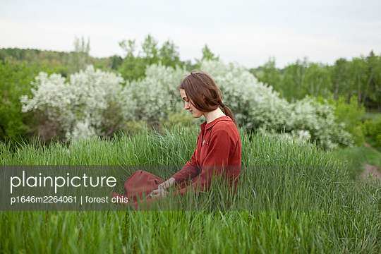 Woman in red dress on a meadow - p1646m2264061 by Slava Chistyakov
