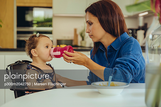 Mother helping baby daughter drinking water from bottle in kitchen - p300m2042750 by Mareen Fischinger