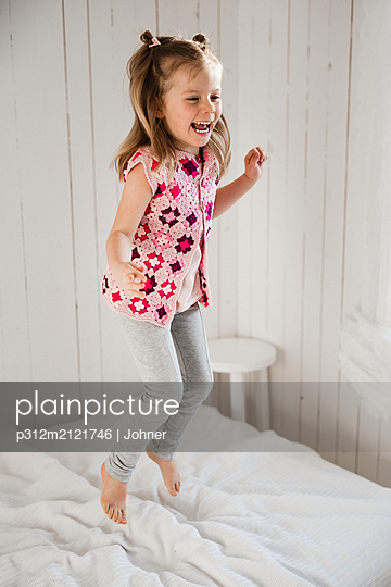 Girl jumping on bed - p312m2121746 by Johner