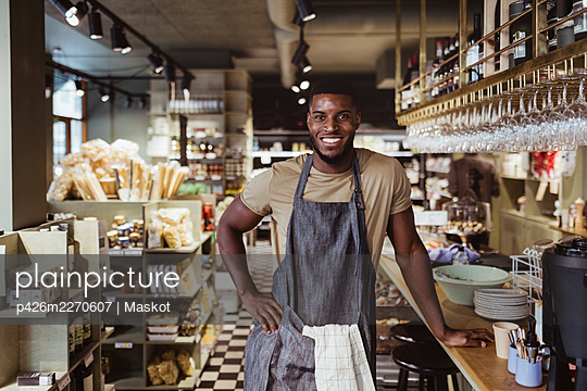 Portrait of smiling male owner with hand on hip standing in delicatessen shop - p426m2270607 by Maskot