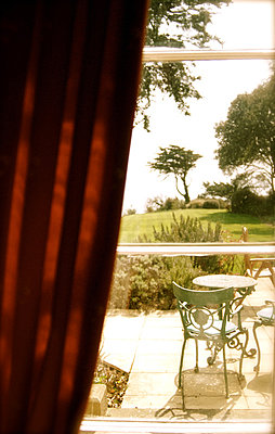 View through a window onto a bistro table in a garden - p1072m829548 by Tracy Jean Shields