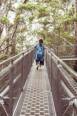 woman in big blue dress climbs along tree top walk in remote australia - p1166m2136720 by Cavan Images