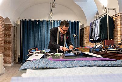Senior dressmaker choosing fabric from catalog - p1166m2261426 by Cavan Images