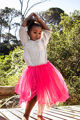 Little girl in pink tulle skirt practices dance pose - p1640m2246803 by Holly & John