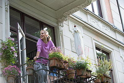 Blonde woman on her balcony - p1678m2258820 by vey Fotoproduction