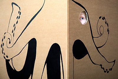 Girl peeking out of cardboard box painted with an octopus - p300m1449566 by Petra Stockhausen