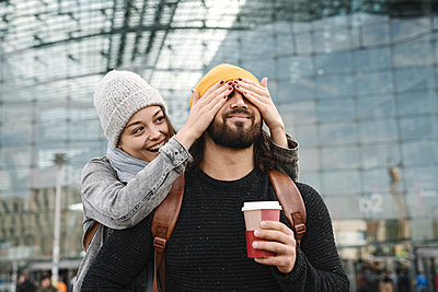 Happy young woman surprising boyfriend at the central station, Berlin, Germany - p300m2155168 by Hernandez and Sorokina
