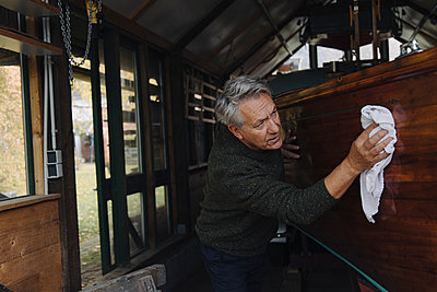 Senior man cleaning wooden boat in a boathouse - p300m2156256 by Gustafsson