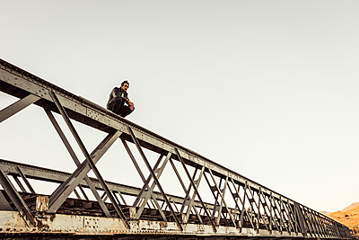 Man crouching on metal bar of an old railway bridge - p300m2180797 by Floco Images