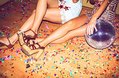 Female friends sitting on floor covered with confetti in party - p300m2206671 by klublu
