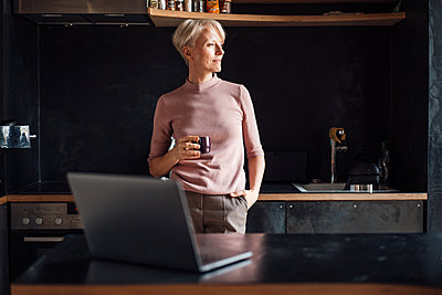 Female entrepreneur with hands in pockets looking away while having coffee in kitchen in home office - p300m2267822 by Robijn Page