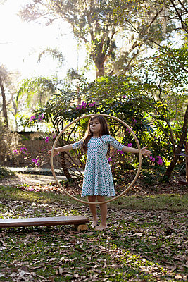 Girl playing with hula hoop in shaded garden - p924m1468818 by Kinzie Riehm