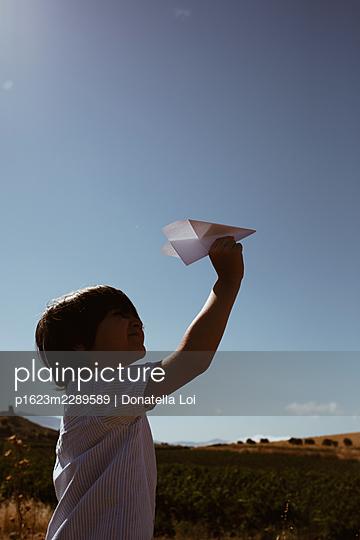 Kleiner Junge mit Papierflieger - p1623m2289589 von Donatella Loi