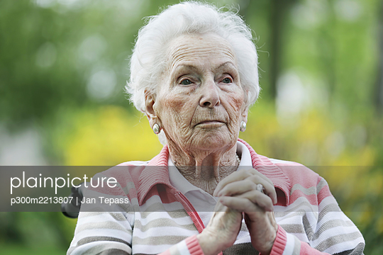 Germany, North Rhine Westphalia, Cologne, Senior woman sitting on wheelchair - p300m2213807 by Jan Tepass