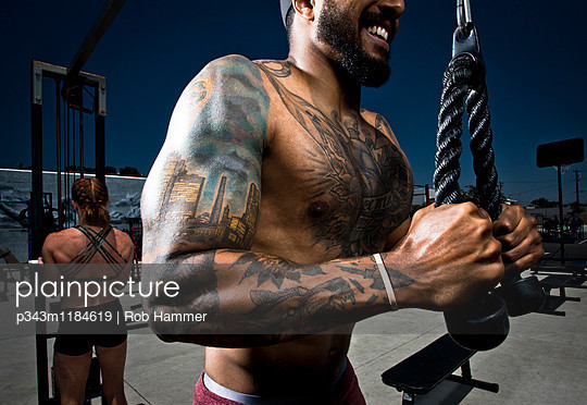 An athletic guy with tattoos works out his triceps.