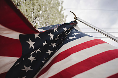 Low angle view of American flag against sky at park - p1166m2000631 by Cavan Images