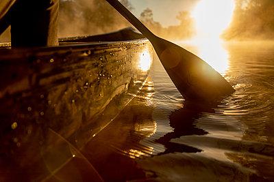 Sunrise canoe ride on foggy river. - p1166m2269652 by Cavan Images