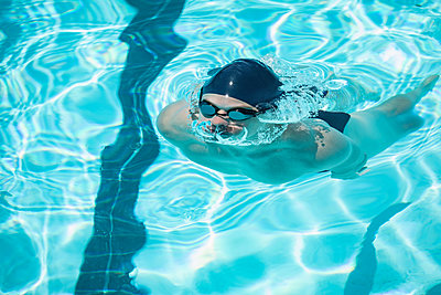 Young swimmer swimming in pool - p1315m2091045 by Wavebreak