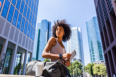 Germany, Frankfurt, portrait of young woman with travelling bag, tablet and coffee to go in the city - p300m2030333 von Tom Chance