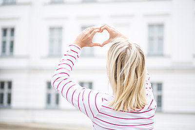 Rear view of young blond woman making heart shape with hands and fingers - p300m2140498 by Jean Schwarz