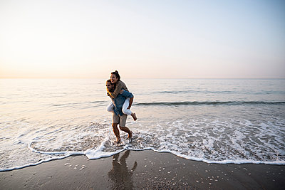 Cheerful man giving piggyback to girlfriend while walking on shore at beach against clear sky during sunset - p300m2226540 by Uwe Umstätter
