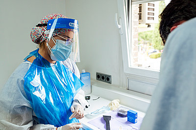 Dental health professionals wearing protective face mask and face shield working while standing at clinic during Covid-19 - p300m2240724 by Jose Luis CARRASCOSA