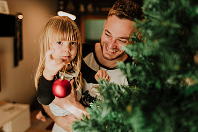 Smiling father carrying girl while holding ornament by Christmas tree - p300m2252061 by Gala Martínez López