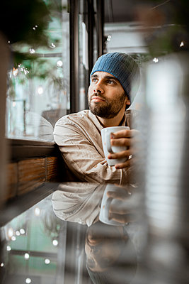 Handsome man with coffee cup day dreaming in cafe - p300m2276338 by Rafa Cortés