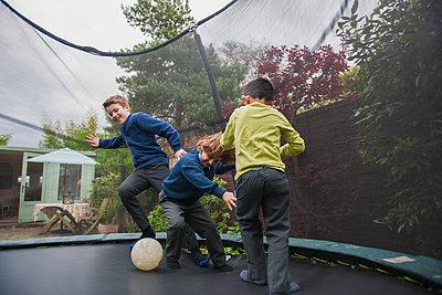 Boys on trampoline playing football - p429m1469388 by G. Mazzarini