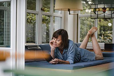 Brunette woman using IPad computer on the sofa - p586m2134822 by Kniel Synnatzschke