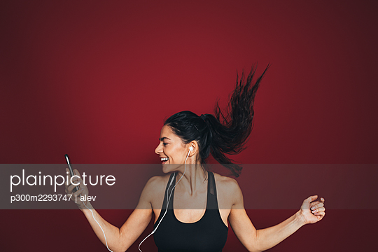Cheerful mid adult female sportsperson listening music through in-ear headphones - p300m2293747 by alev