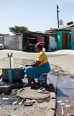 Frau sitzt am Wasserhahn - p045m1362812 von Jasmin Sander