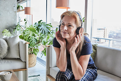 Smiling mature woman looking away while listening music through headphones on sofa at home - p300m2266054 by Jo Kirchherr
