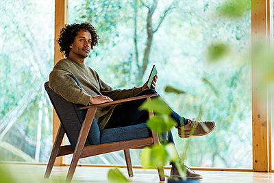 Young man with digital tablet looking away while sitting on armchair by window at front yard - p300m2268020 by Steve Brookland