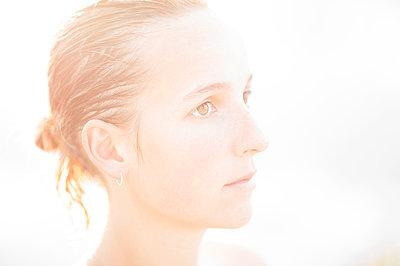 Porträt einer jungen Frau im Gegenlicht - p552m2194529 von Leander Hopf