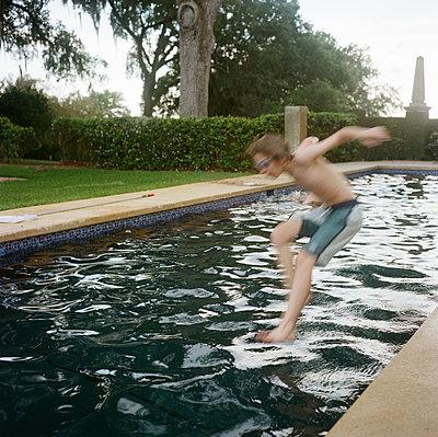 Boy jumping into Pool - p635m1488510 by Julia Kuskin
