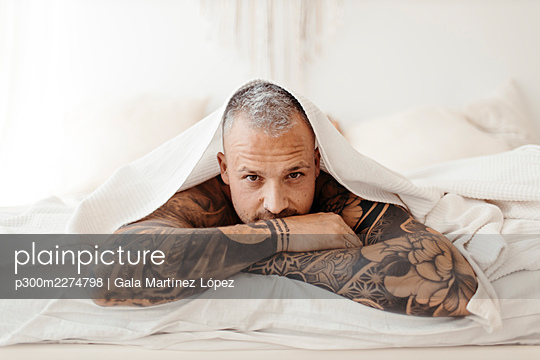 Handsome man lying on bed at home - p300m2274798 by Gala Martínez López