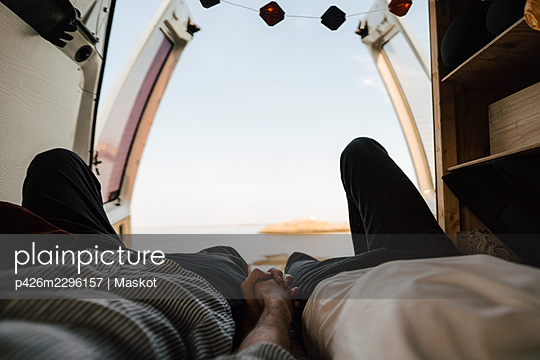 Midsection of gay couple holding hands while resting in camping van at lakeshore - p426m2296157 by Maskot
