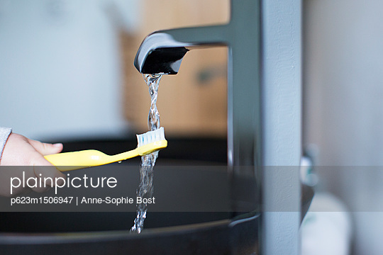 Child holding toothbrush under water faucet - p623m1506947 by Anne-Sophie Bost